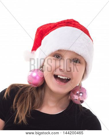 Happy teenager girl in a Santa Claus hat and Christmas balls instead of earrings