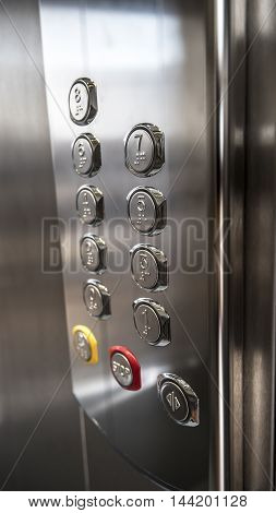 nine floors building metallic elevator buttons closeup