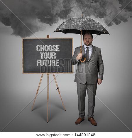 Choose your future text on blackboard with businessman holding umbrella
