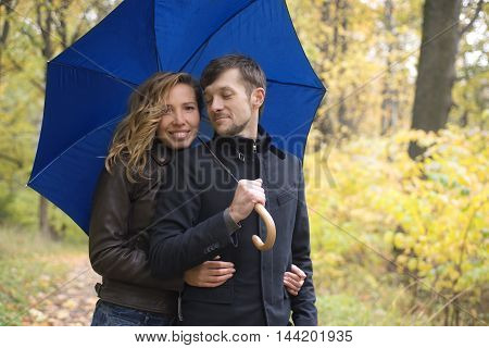 A loving couple standing under an umbrella in the autumn forest