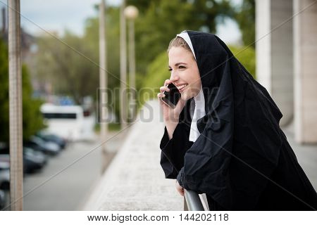 Young nun in black dress calls phone - outdoors setting