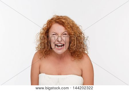 Mature Caucasian woman yelling with angry expression. Picture of furious mature woman posing isolated on white in studio.