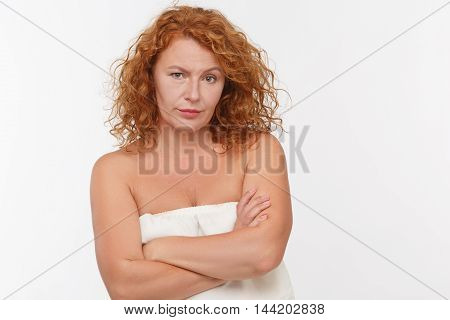Portrait of distrustful mature woman posing with her arms crossed or folded isolated on white background in studio. Emotions concept.
