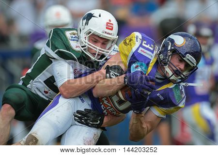 VIENNA, AUSTRIA - MAY 17, 2015: CB Christian Koeppe (#21 Unicorns) tackles WR Dominik Bundschuh (#3 Vikings) in a game of the Big Six Football League. in a game of the Big Six Football League.