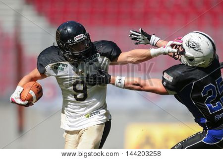 KLAGENFURT, AUSTRIA - JULY 11, 2015: LB Lukas Lamprecht (#25 Devils) tackles RB Anton Wegan (#09 Rangers) in a game of the Division I of the Austrian Football League.