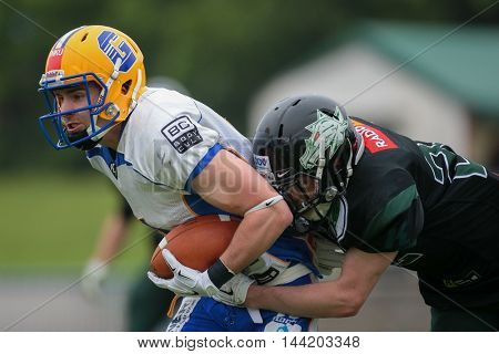 VIENNA, AUSTRIA - MAY 3, 2015: FS Thomas Meznik (#22 Dragons) tackles WR Philipp Sommer (#4 Giants) in a game of the Austrian Football League.