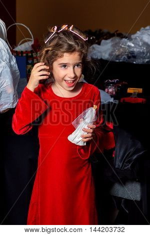 A young girl in a red velvet dress feels the curl in her hair after a curler is removed. Her facial expression is one of unexpected excitement or happiness.