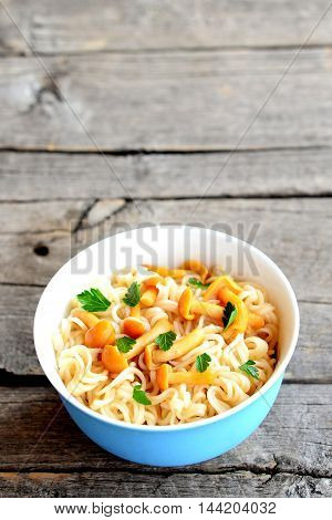 Pasta with mushrooms and fresh herbs recipe. Pasta with marinated chanterelles in a bowl isolated on old wooden background. Vegetarian dish. Closeup