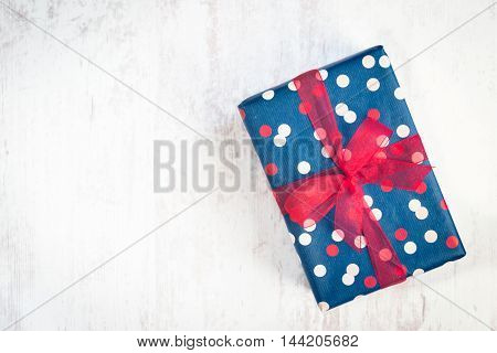Gift box wrapped in blue dotted paper with red ribbon on a white wood old background