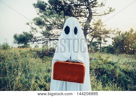 Cute ghost with suitcase walking in the forest. Theme of Halloween and magic