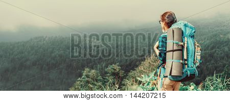 Hiker young woman with backpack looking at the mountains in summer. Toned image
