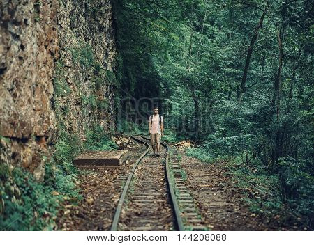 Traveler young man walking on railroad in summer gorge near the cliff