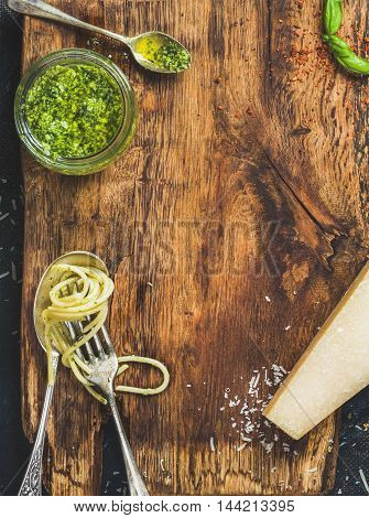 Italian cuisine cooking background. Jar with pesto sauce, spoon and fork with cooked spaghetti, fresh basil leaves and Parmesan cheese on rustic wooden board texture. Top view, copy space