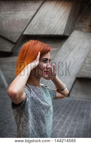beautiful redhead girl wearing in a gray dress posing against a background of a concrete wall.