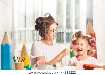 Little girl eating ice cream with her mother on white