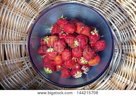 strawberries in blue glass plate on wicker table top