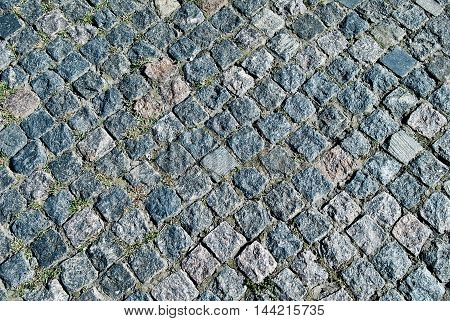 Stone pavement texture. Granite cobblestoned pavement background. Abstract background of old cobblestone.