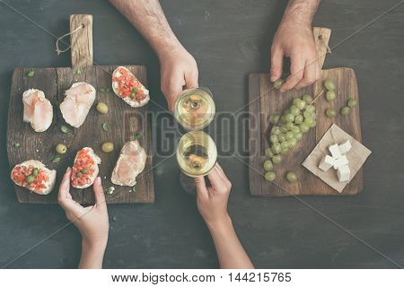 Couple drinking white wine with snacks for wine on a dark background top view