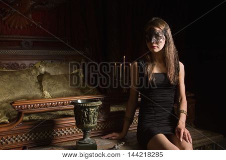 Fashion Sexy Brunet Woman Wearing Black Dress And Mask At Bedroom