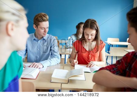 education, learning and people concept - group of students with books at school lesson