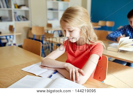 education, learning and people concept - student girl with book and notebook at school lesson