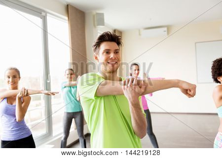 fitness, sport, training and exercising concept - group of smiling people stretching in gym