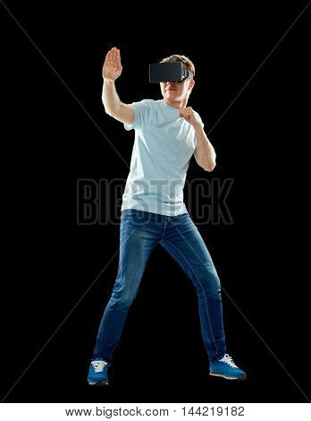 3d technology, virtual reality, entertainment, cyberspace and people concept - young man with virtual reality headset or 3d glasses playing game and fighting