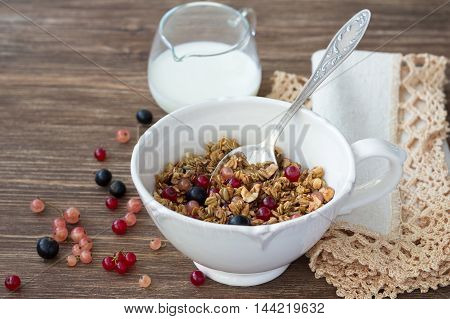 Homemade delicious healthy granola with nuts, seeds, honey and fresh berries in a ceramic cup on a wooden table