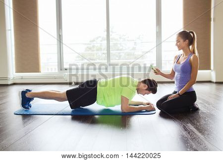 fitness, sport, technology and people concept - man and woman with smartphone doing plank exercise on mat in gym