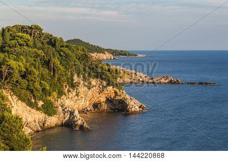 A view along the coast in Dubrovnik during the summer showing the cliffs and sea