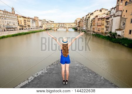 Young female traveler in blue dress and hat standing with raised hands in front of the famous arch bridge in Florence in Italy