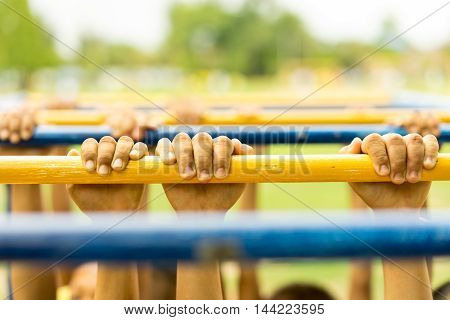 Children playing and swinging along on Monkey Bars outdoors soft focus