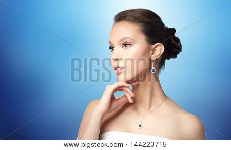 beauty, jewelry, wedding accessories, people and luxury concept - beautiful asian woman or bride with earring and pendant over blue background