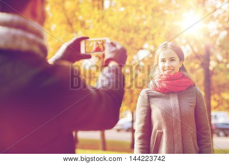 love, relationship, family and people concept - smiling couple hugging and taking selfie with smartphone in autumn park