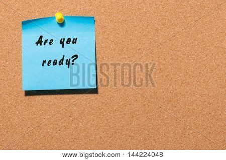 Are You Ready, written on an blue sticky note on a cork bulletin board. With empty space for text.