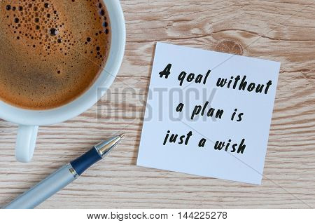 a goal without a plan is just a wish - motivational handwriting on a napkin with a cup of morning coffee.