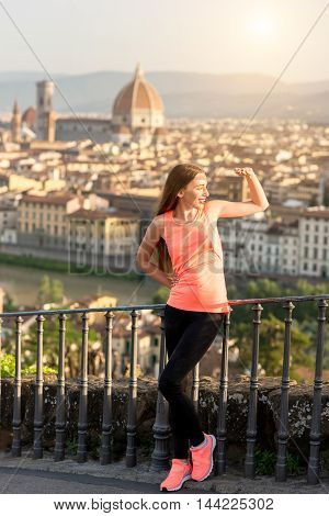 Young woman in sportswear resting after morning exercise on the old city background in Florence in Italy