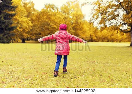 season, childhood, imagination, happiness and people concept - happy little girl running and having fun in autumn park from back