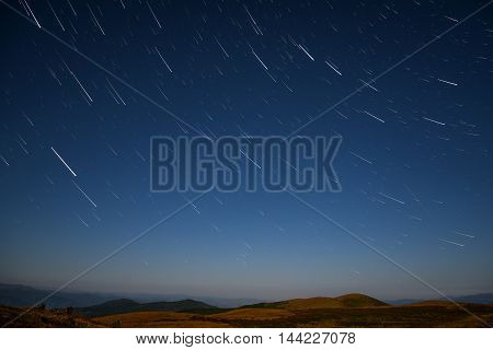 Beautiful night landscape with traces of stars in the night sky against a background of mountains shot in the high mountains with a long exposure