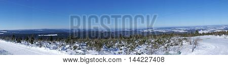 Panorama views from peak of the Fichtelberg on the Erzgebirge, snowy winter landscape in Saxony Germany, blue cloudless sky, panoramic