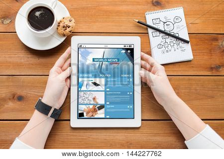 business, education, technology and people concept - close up of woman with internet news application on tablet pc computer screen, notebook and coffee on wooden table