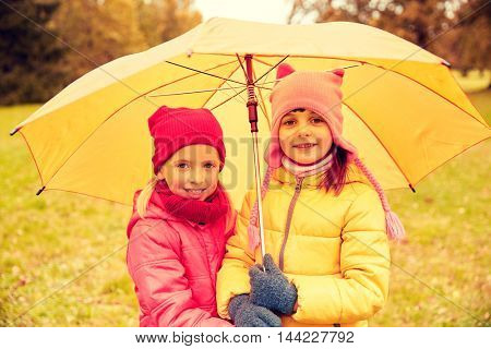childhood, friendship, season, weather and people concept - happy little girls with umbrella in autumn park