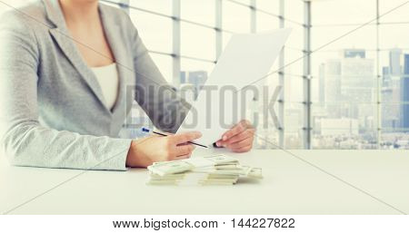 business, finance, tax and people concept - close up of woman hands with us dollar money and tax report paper form over city office room background