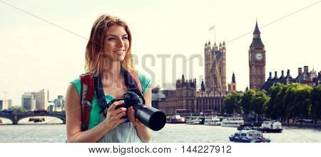 travel, tourism and people concept - happy young woman with backpack and camera photographing over london city street and big ben tower background