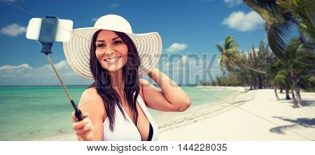 lifestyle, leisure, summer, technology and people concept - smiling young woman or teenage girl in sun hat taking picture with smartphone on selfie stick over tropical beach with palms background