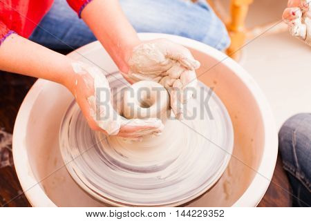 Hands of girl who tries to make pottery from white clay on a potter's wheel