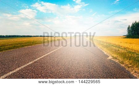 Perspective view of endless rural road and blue cloudy sky in summer shiny day