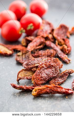 Tasty dried tomatoes on kitchen table.