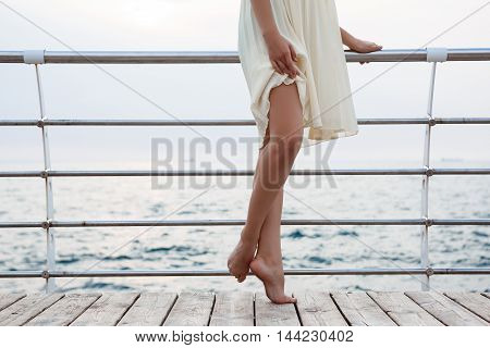 Young beautiful ballerina dancing and posing outside early in morning, sea background. Close up of legs.