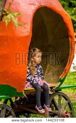 Little Girl Playing In The Pumpkin Carriage In The Daytime
